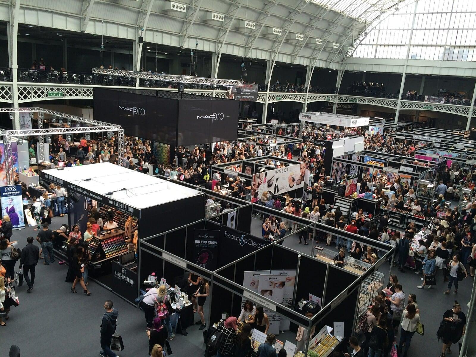 A large open and airy exhibition hall with multiple trade stands and busy attendees.